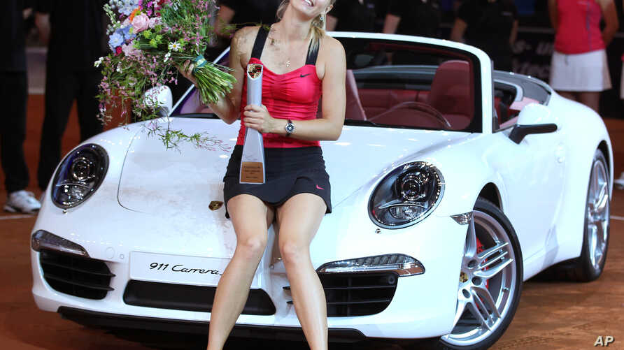 FILE - Russia's Maria Sharapova sits on a Porsche Carrera after beating Belarus' Victoria Azarenka in the final of the Porsche Tennis Grand Prix in Stuttgart, Germany, Apr. 29, 2012.