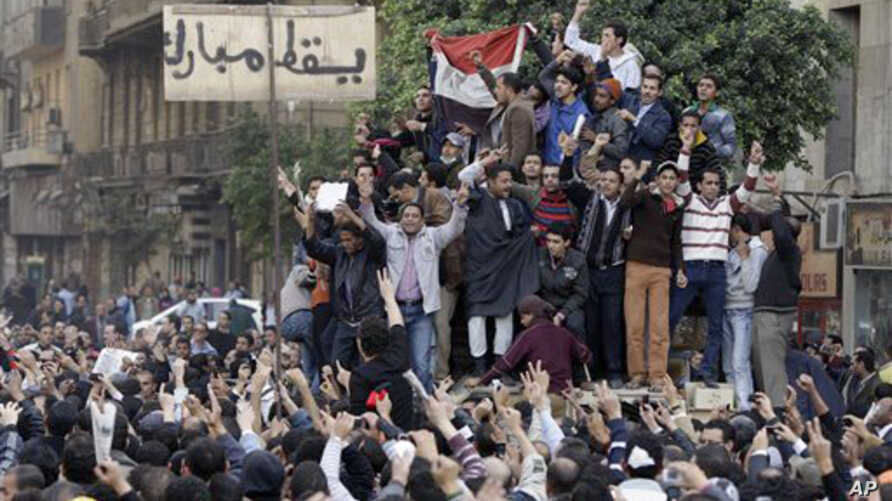 "Egyptian anti-government protesters climb atop an Egyptian army armored personnel carrier, next to a signpost bearing the words ""Down Mubarak"", in Cairo,January 29, 2011"