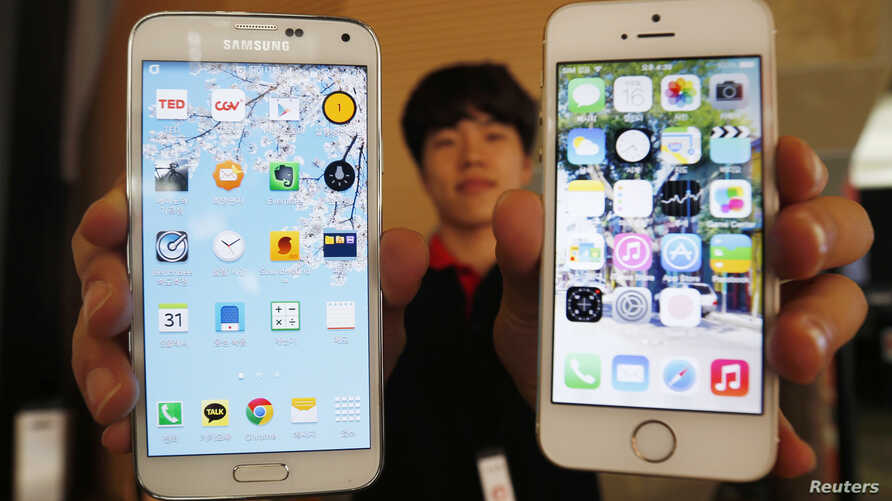 A sales assistant holding Samsung Electronics' Galaxy 5 smartphone (L) and Apple Inc's iPhone 5 smartphone (R) poses for photographs at a store in Seoul, July 16, 2014.