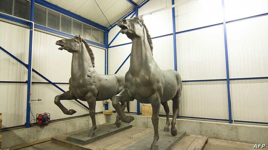 """Horse sculptures """"Walking Horses"""" by Austrian-German sculpturer Josef Thorak are shown in a police warehouse in Bad Bergzabern, central Germany, made available May 22, 2015."""