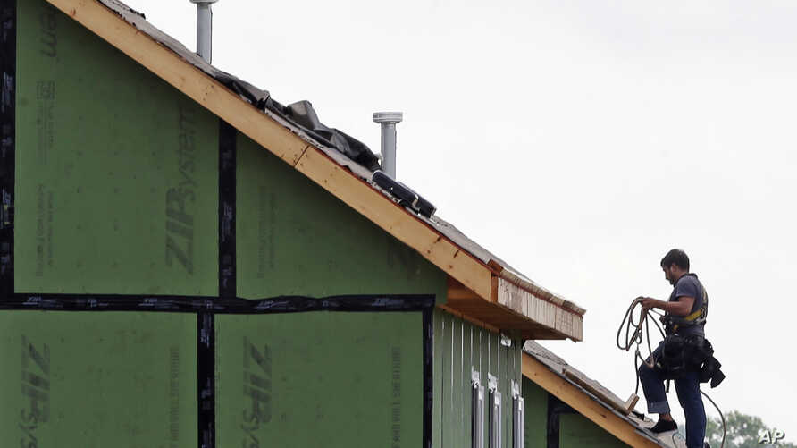 A roofer works on a home under construction in the Briar Chapel community in Chapel Hill, N.C., June 9, 2015.