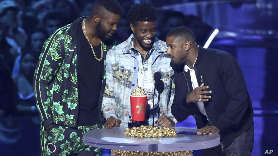 "In this Saturday, June 16, 2018, photo, Winston Duke, from left, Chadwick Boseman and Michael B. Jordan accept the award for best movie for ""Black Panther"" at the MTV Movie and TV Awards in Santa Monica, Calif."