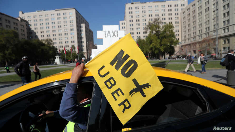 "FILE - A taxi driver holds a flag reading ""No more Uber"" during a nationwide strike to protest against Uber Technologies in Santiago, Chile."