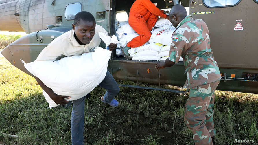 Workers offload food aid from a South African National Defence Force helicopter in the aftermath of Cyclone Idai in Buzi, near Beira, Mozambique, March 25, 2019.