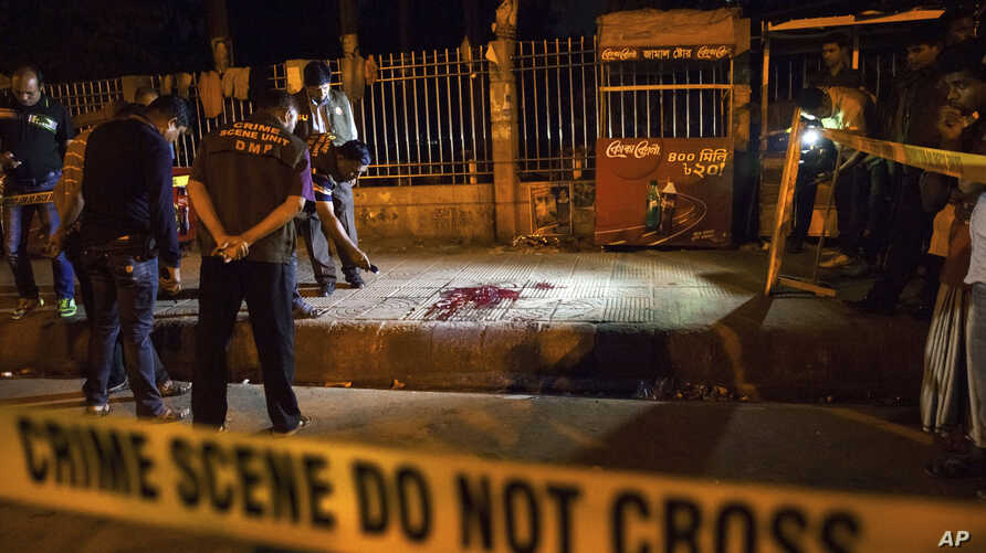 FILE - Bangladeshi policemen investigate at the site of attack on Bangladeshi-American blogger Avijit Roy, in Dhaka, Bangladesh, Feb. 26, 2015.