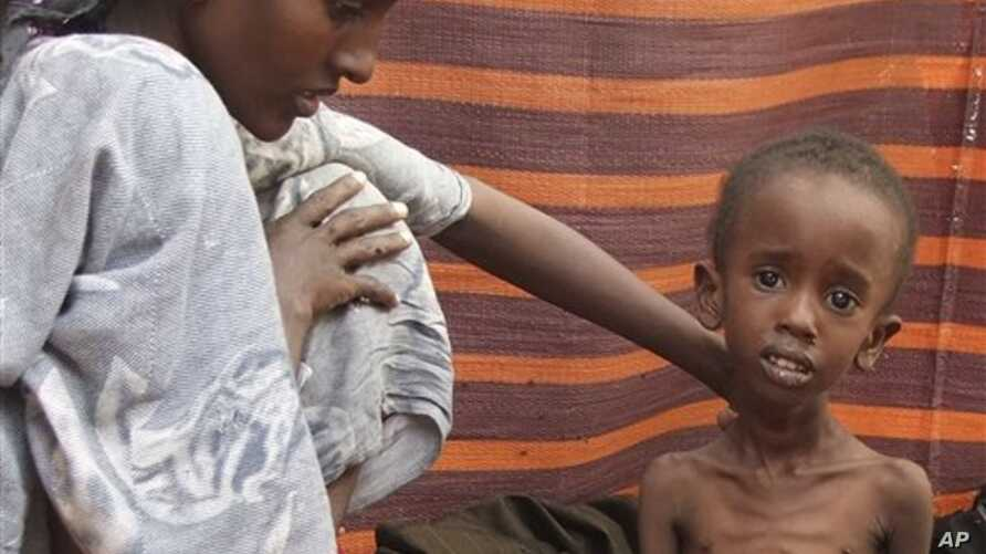 A refugee woman from southern Somalia attends to her malnourished child in their makeshift shelter in a refugee camp in Mogadishu, Somalia, Aug. 6, 2011