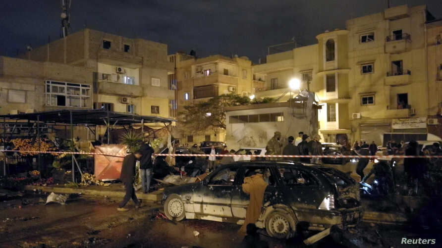 People gather at the site of twin car bombs in Benghazi, Libya, Jan. 23, 2018.