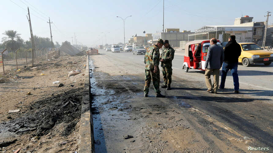 Iraqi security forces stand at the site of car bomb attack in the predominately Shi'ite Muslim neighbourhood of al-Obaidi, Iraq, Jan. 5, 2017.