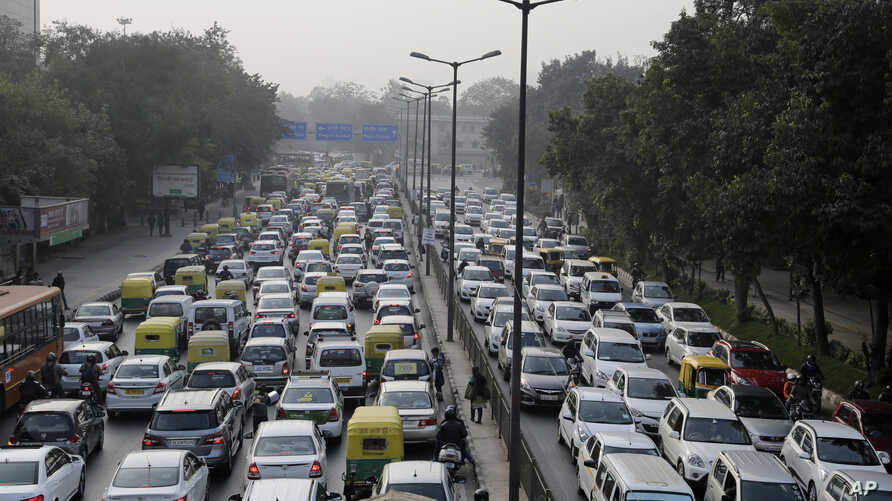 FILE - Vehicles move slowly at a traffic intersection after the end of a two-week experiment to reduce the number of cars to fight pollution in in New Delhi, India, Jan. 16, 2016.