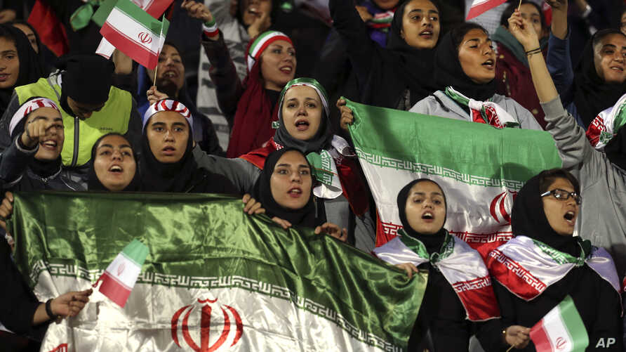 Female Iranian spectators cheer as they wave their country's flag during a friendly soccer match between Iran and Bolivia, at the Azadi (Freedom) stadium, in Tehran, Iran, Oct. 16, 2018.