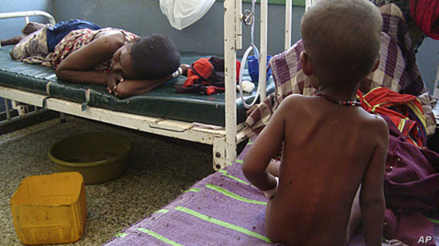 A malnourished child from southern Somalia sits on the bed at Banadir hospital in Mogadishu, Somalia, August 2, 2011