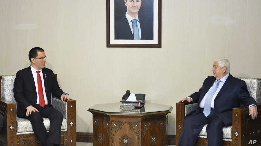 In this photo released by the Syrian official news agency SANA, Syria's Foreign Minister Walid al-Moallem, right, meets with his Venezuelan counterpart Jorge Arreaza, in Damascus, April 4, 2019.
