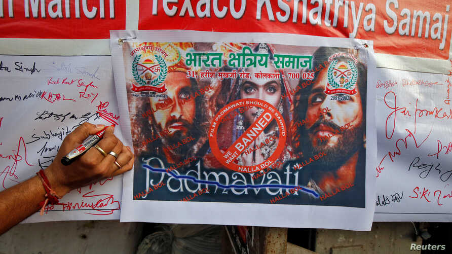 """A man signs a banner during a signature campaign as part of a protest against the release of Bollywood movie """"Padmavati"""" in Kolkata, India, Nov. 22, 2017."""