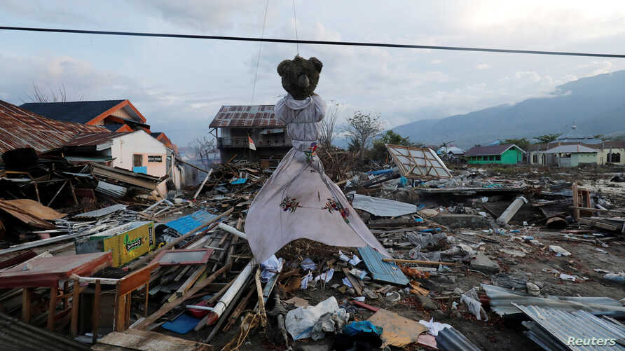 A teddy bear hangs next to earthquake and tsunami damaged property along the waterfront in Palu, Central Sulawesi, Indonesia, Oct. 10,  2018.