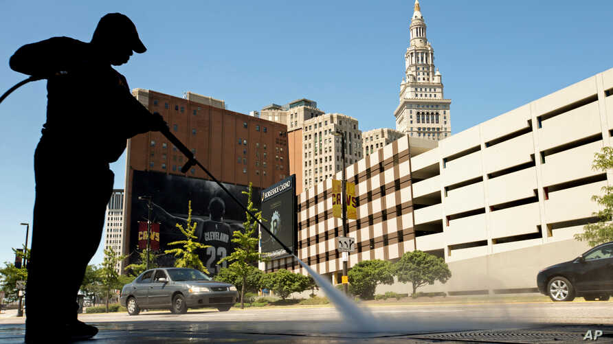 A worker cleans the sidewalk in front of the Quicken Loans Arena in Cleveland,  Aug. 5, 2015, before Thursday's first Republican presidential debate being held at the arena.
