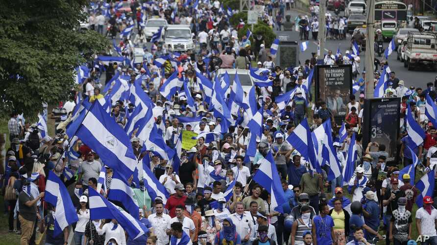 People march with Nicaraguan national flags during the commemoration of Student Day, demanding the ouster of President Daniel Ortega and the release of political prisoners, in Managua, July 23, 2018.