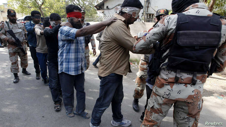 Paramilitary soldiers escort blindfolded men, who were detained during  a raid on the Muttahida Qaumi Movement political party headquarters, after presenting them before an anti-terrorism court in Karachi, March 12, 2015.