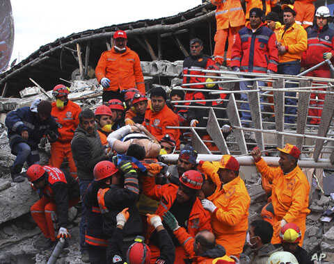 Rescue workers pull out a man from the rubble of a collapsed hotel in Van, eastern Turkey, November 10, 2011.