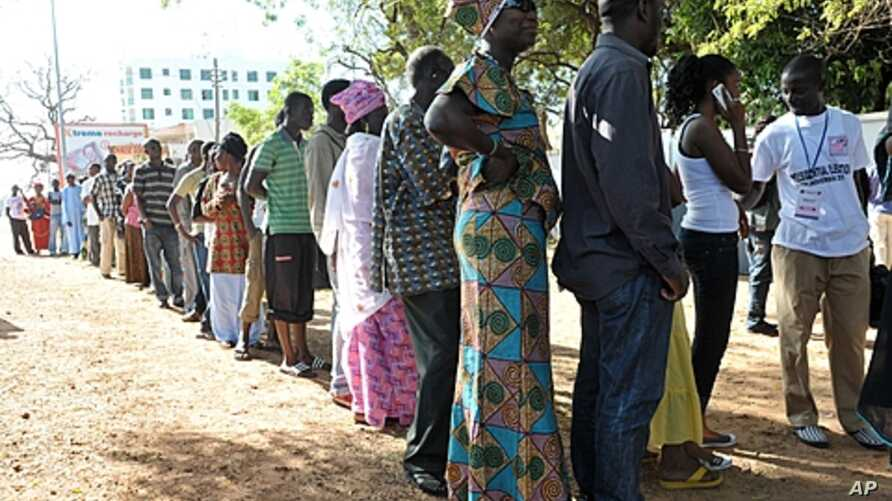 People wait to vote outside a polling station in Serrekunda, southwest the capital Banjul, during the presidential elections, November 24, 2011.