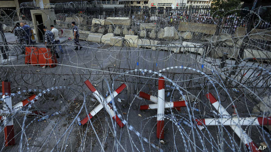 Lebanese policemen check metal barricades and other reinforcements that were installed as extra security measures around the Lebanese government building after anti-government protesters removed barbed wire barriers during recent demonstrations, in B