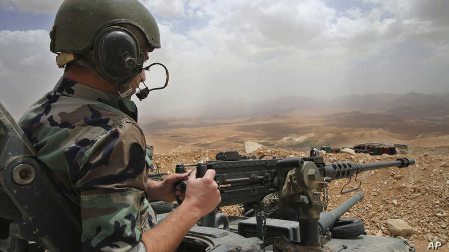 FILE - A Lebanese army soldier sits on a tank near the Syrian border, in northeast Lebanon.