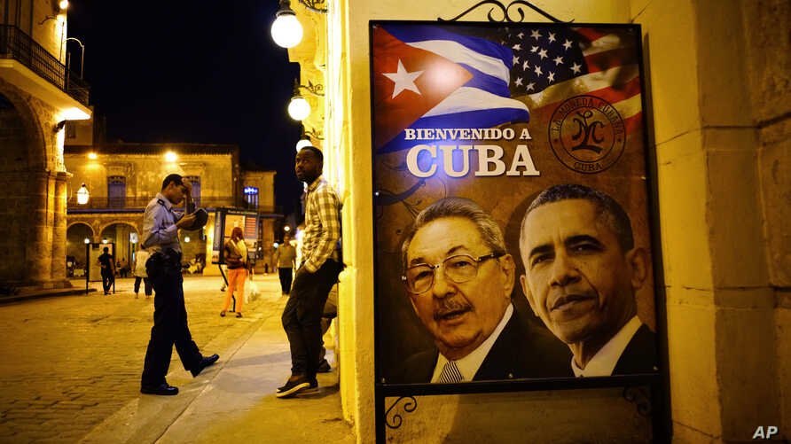 "A poster features portraits of Cuba's President Raul Castro, left, and U.S. President Barack Obama and reads in Spanish ""Welcome to Cuba"" outside a restaurant in Havana, Cuba, March 17, 2016."