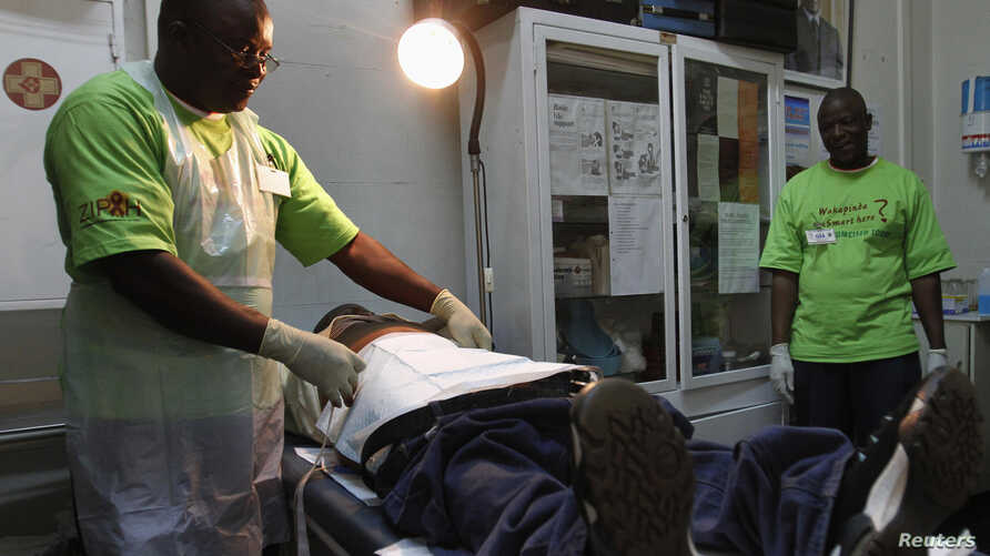 A doctor (L) performs circumcision on an unidentified politician in an effort to reduce the spread of HIV, in Harare, Zimbabwe, June 22, 2012.