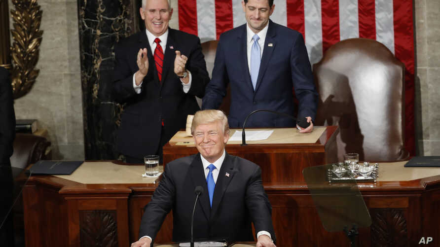 President Donald Trump steps to the podium to begin his State of the Union address to a joint session of Congress on Capitol Hill in Washington, Jan. 30, 2018. Behind Trump are Vice President Mike Pence and House Speaker Paul Ryan of Wisconsin.