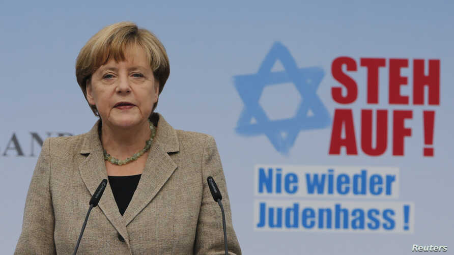 """German Chancellor Angela Merkel, standing in front of a sign that reads """"Stand up!"""" makes an address during an anti-Semitism demonstration at Berlin's Brandenburg Gate, Sept. 14, 2014."""