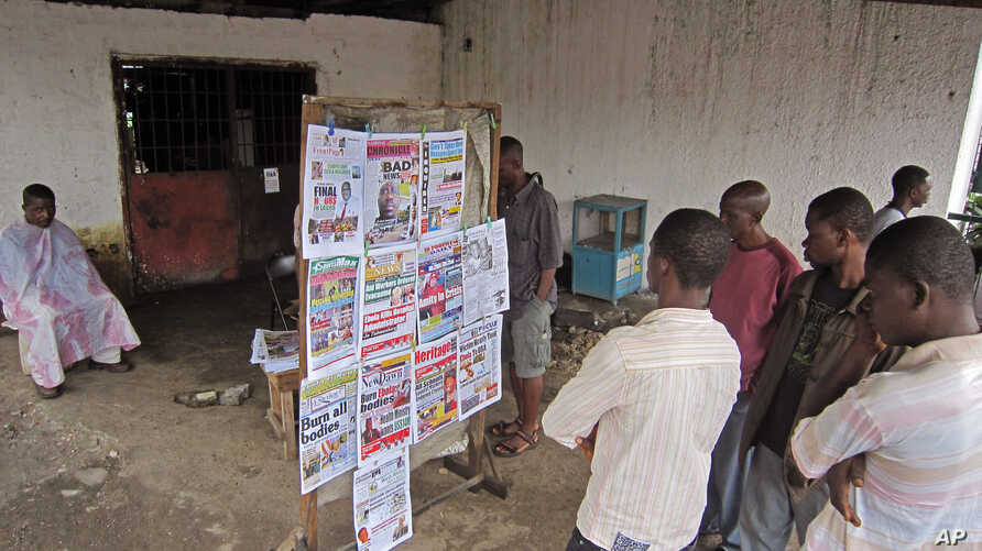 People read local newspaper headlines focusing on the Ebola outbreak, including a newspaper, left,  reading 'Burn all bodies' in the city of Monrovia, Liberia, Thursday, July 31, 2014. The worst recorded Ebola outbreak in history surpassed 700 deaths