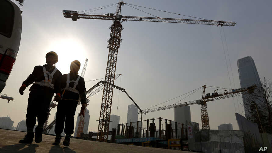 Workers walk out from a construction site at the Central Business District of Beijing, China, Jan. 20, 2015.