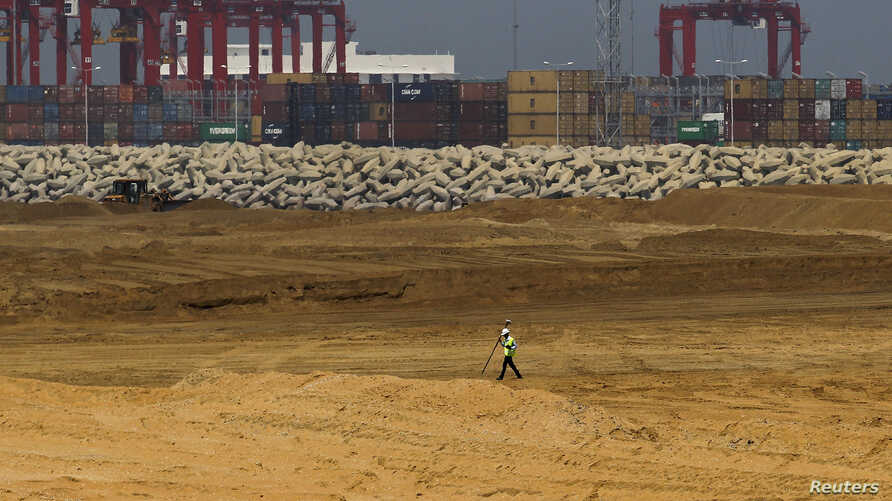 """FILE - An engineer walks through a part of a construction site of Chinese investment """"Colombo Port City"""" in Colombo, February 20, 2015."""
