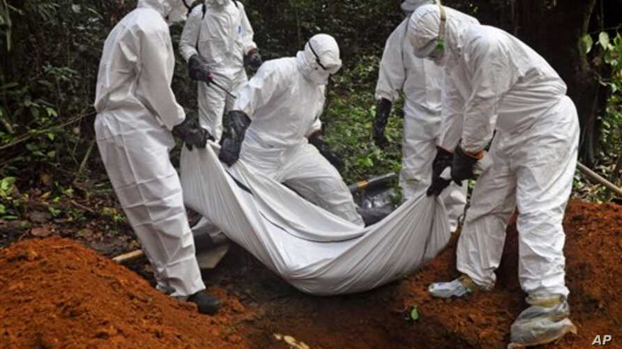 Health workers bury the body of a woman who is suspected of having died of the Ebola virus in Bomi county, on the outskirts of Monrovia, Liberia, Monday, Oct. 20, 2014. Liberian President Ellen Johnson Sirleaf said Ebola has killed more than 2,000 pe