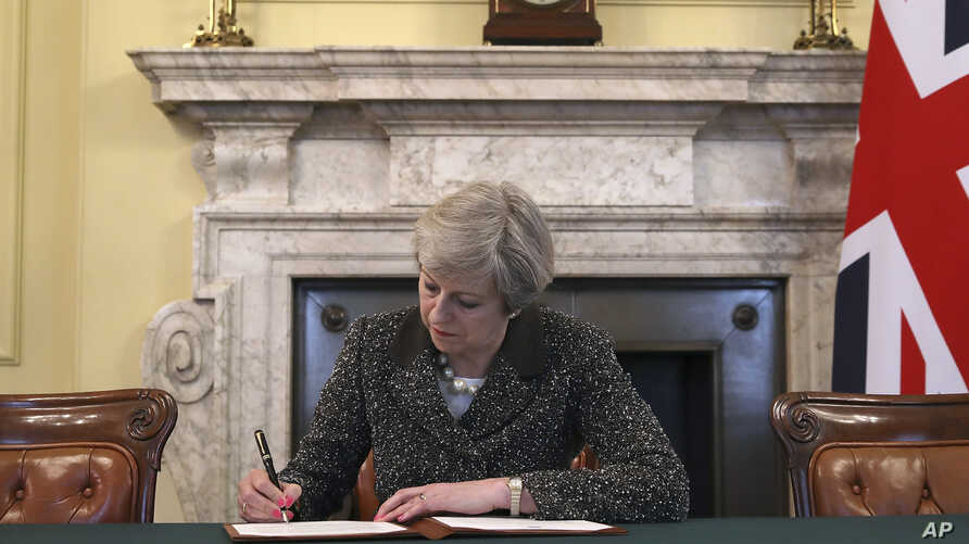 Britain's Prime Minister Theresa May signs the official letter to European Council President Donald Tusk, in 10 Downing Street, London, March 28, 2017, invoking Article 50 of the bloc's key treaty, the formal start of exit negotiations. Britons voted...