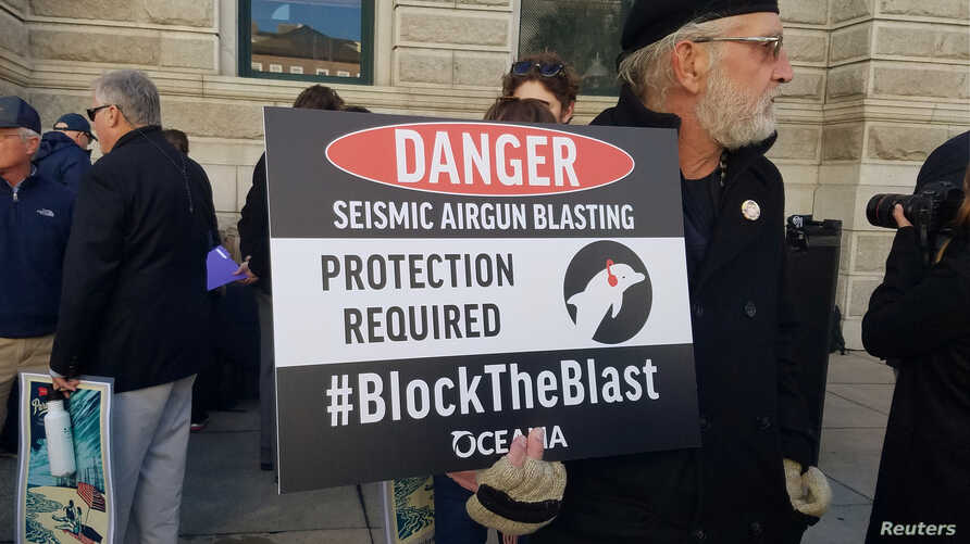 South Carolina coastal resident Phil Frandino holds a sign at the Charleston announcement of a lawsuit against the Trump administration to stop future seismic airgun testing in the Atlantic Ocean, in Charleston, S.C., Dec. 11, 2018.