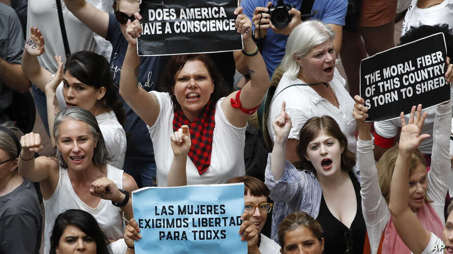 Women hold signs as they protest the separation of immigrant families, June 28, 2018, inside the Hart Senate Office Building on Capitol Hill in Washington.