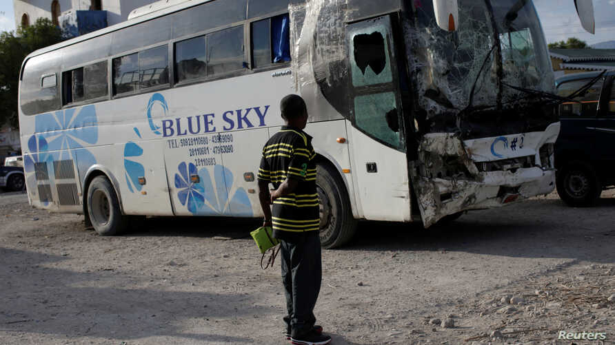 A man looks at a bus that drove into a parade of pedestrians in Gonaives, Haiti, March 12, 2017.
