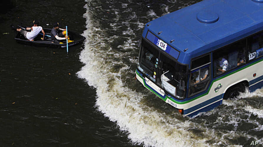 Residents travel on a boat as a bus drives on a flooded street in Bangkok, Thailand, November 5, 2011.
