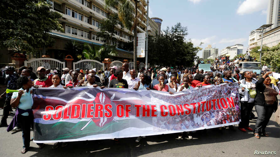FILE - Members of Kenya's ruling Jubilee coalition carry a banner as they demonstrate in support of the Independent Electoral and Boundaries Commission (IEBC) the electoral body ahead of next year's election in Nairobi, Kenya, June 8, 2016.