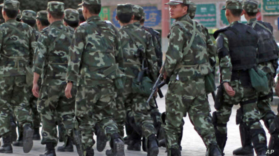 Armed police officers patrol an ethnice Uighur area in Kashgar, in Xinjiang province Aug. 4, 2011.