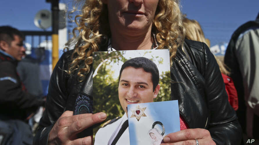 The wife of sailor Fernando Villarreal, a crew member of the missing submarine, shows his picture as she prays at the naval base in Mar de Plata, Argentina, Friday, Nov. 24, 2017.