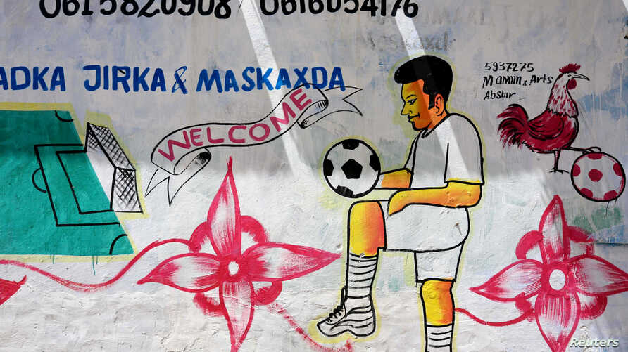 FILE - A mural depicting a soccer player is seen on a wall of a stadium in Hodan district of Mogadishu, Somalia, June 13, 2017.
