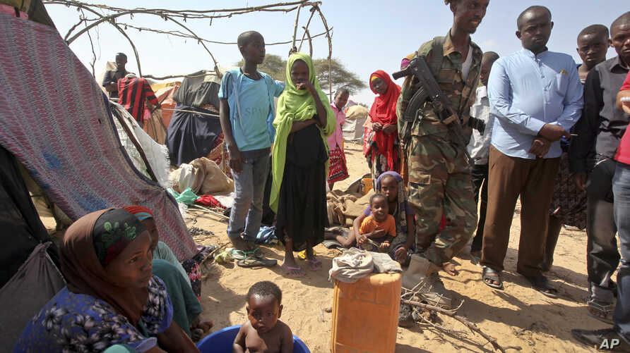 A Somali soldier provides security as newly displaced Somalis gather at a camp on the outskirts of Mogadishu, Somalia, March 28, 2017. A new report says cross-border airstrikes by Kenya have been targeting civilians in pastoral communities in Somalia