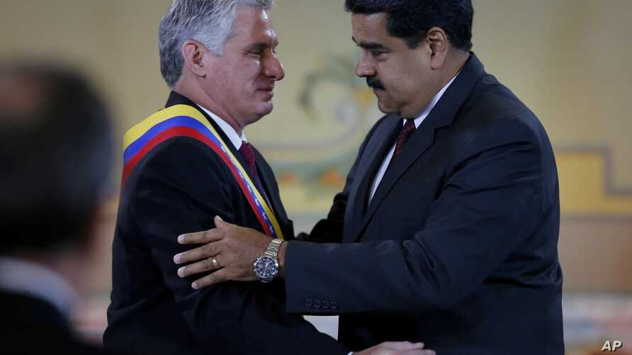 "Cuba's President Miguel Diaz-Canel, left, is embraced by his Venezuelan counterpart Nicolas Maduro after being awarded the ""Orden del Libertador Simon Bolivar,"" at Miraflores Presidential Palace in Caracas, Venezuela, May 30, 2018."
