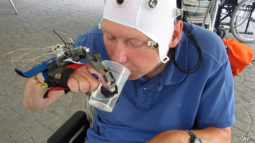 In this undated grab taken from video, a patient uses a robotic hand to drink from a cup, in Badalona, Spain.