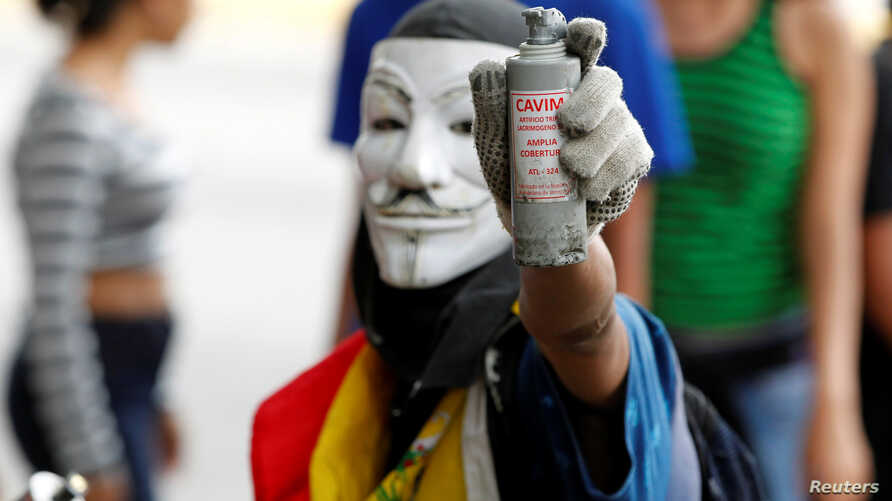 """An opposition demonstrator shows a tear gas grenade while clashing with riot police during the so called """"mother of all marches"""" against Venezuela's President Nicolas Maduro in Caracas, Venezuela, April 19, 2017."""
