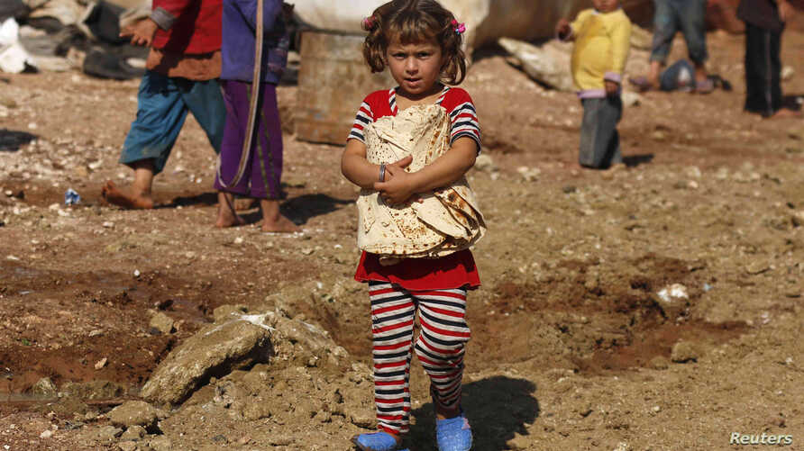 A girl carries bread outside the tents in the Bab Al-Salam refugee camp in Azaz, Oct. 27, 2014.