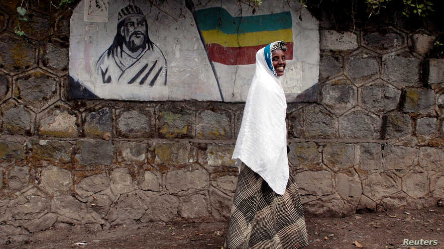 FILE: A traditionally-dressed Ethiopian woman walks past a mural depicting Ethiopia's Emperor Tewodros II in Addis Ababa, Ethiopia, June 1, 2007