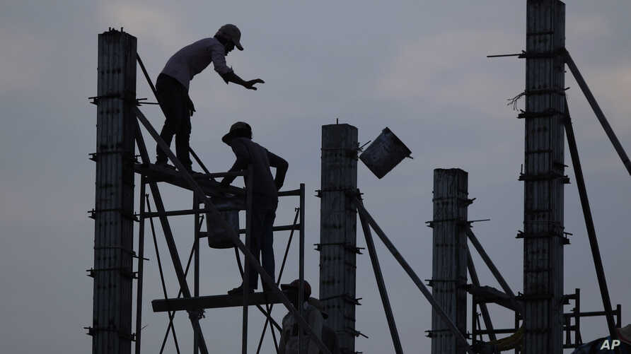 FILE - Workers on scaffolding are silhouetted at a construction site near Phnom Penh, Cambodia, March 21, 2017.