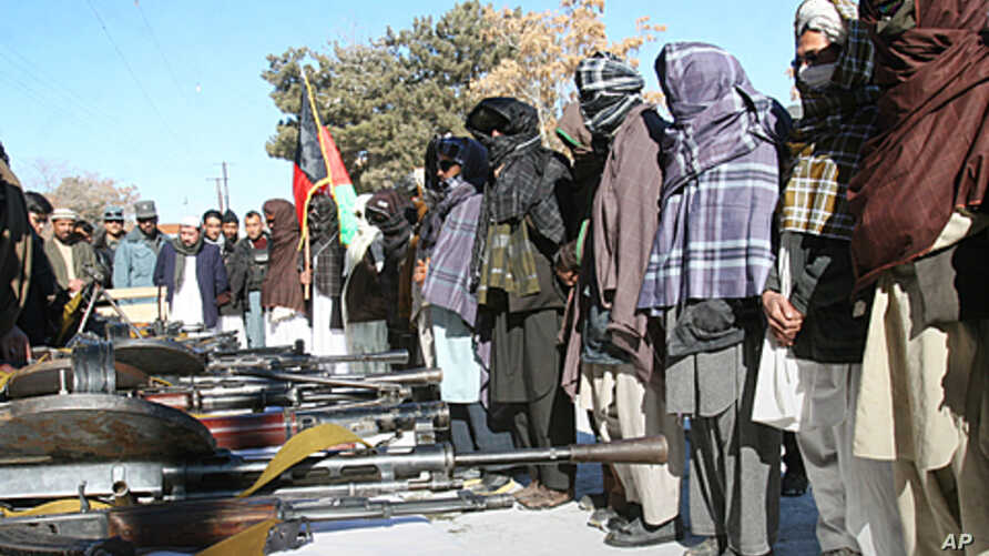 A former Taliban militant, center,  holds the national flag of Afghanistan as others stand while they are seen during a joining ceremony with the Afghan government in Ghazni, west of Kabul, Afghanistan, January 16, 2012.